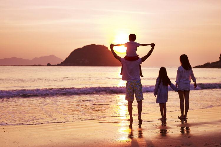 Glückliche Familie im Urlaub am Strand bei Sonnenuntergang