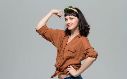 Selbstbewusste und glückliche Frau zeigt ihren Bizeps zum Ausdruck der Stärke