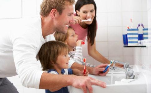 Eltern putzen gemeinsam mit ihren Kleinkindern die Zähne im Bad