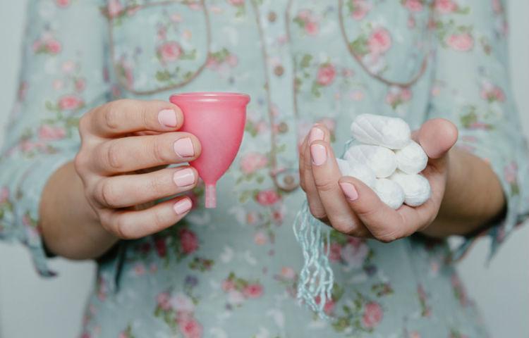 Eine Frau haelt Tampons und eine Menstruationstasse in den Haenden