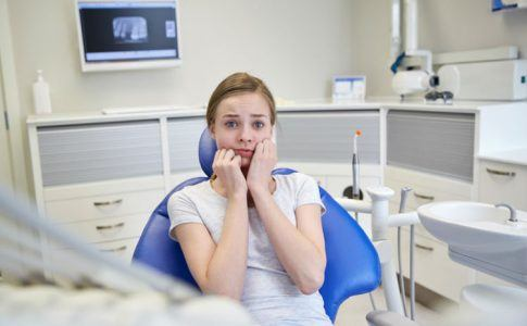 Junge Frau hat Angst beim Zahnarzt