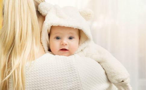 Mutter trägt Baby auf dem Arm, das warm angezogen ist