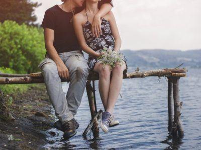 ein junges Paar sitzt auf einem Steg am See