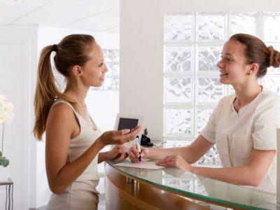 junge Frau an Arztrezeption