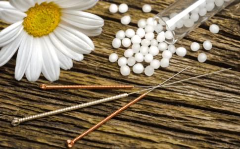 Drei Akupunkturnadeln angerichtet auf einem Holzuntergrund mit weißen Kugeln und einer Blume