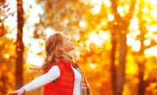 Glückliche Frau genießt die herbstlichen Farben des Waldes