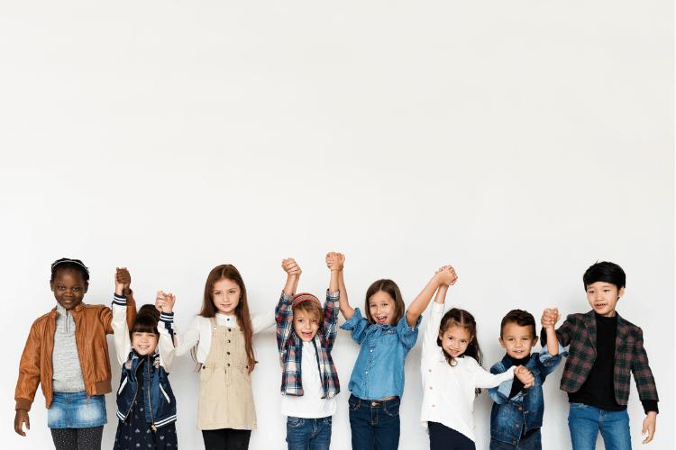 Mehrere Kinder vor einer weißen Wand in moderner Kindermode