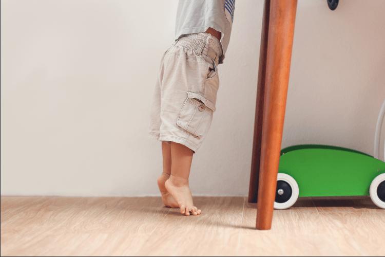 Ein Kind auf Zehenspitzen, das scheinbar versucht etwas zu greifen