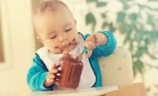 Baby nascht Schokoladencreme im Babystuhl