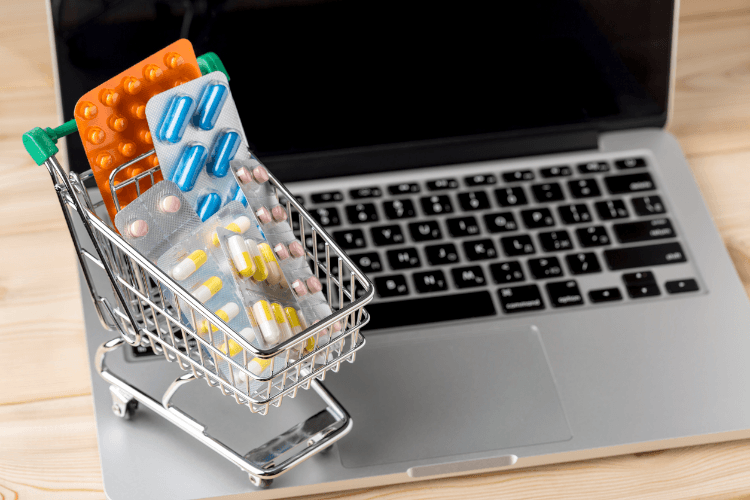 Kleiner Einkaufswagen mit verschiedenen Medikamenten auf einem Notebook