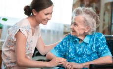 Eine junge Frau kümmert sich um eine ältere Frau im Rollstuhl