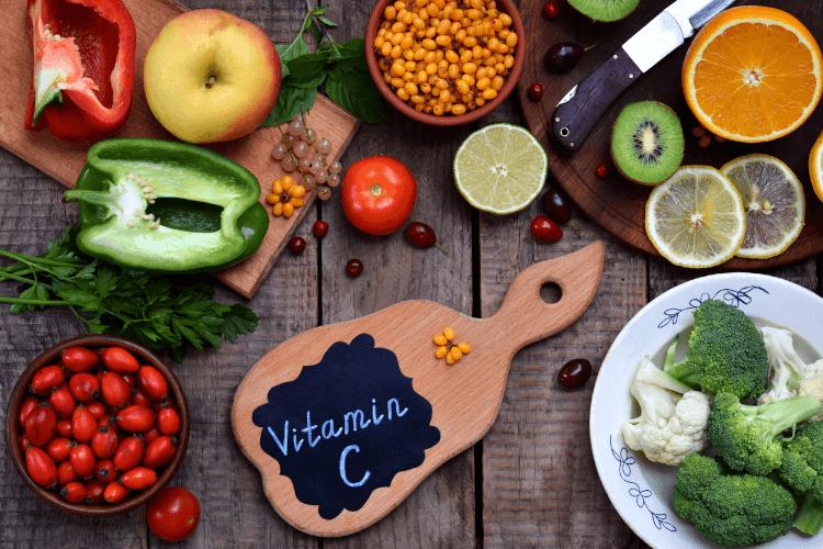 Verschieden Obst- und Gemüsesorten und ein Brett mit der Aufschrift Vitamin C auf einer Holzunterlage