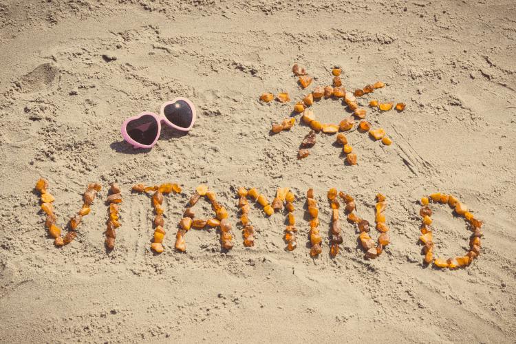 Vitamin D Schriftzug aus Steinen am Strand