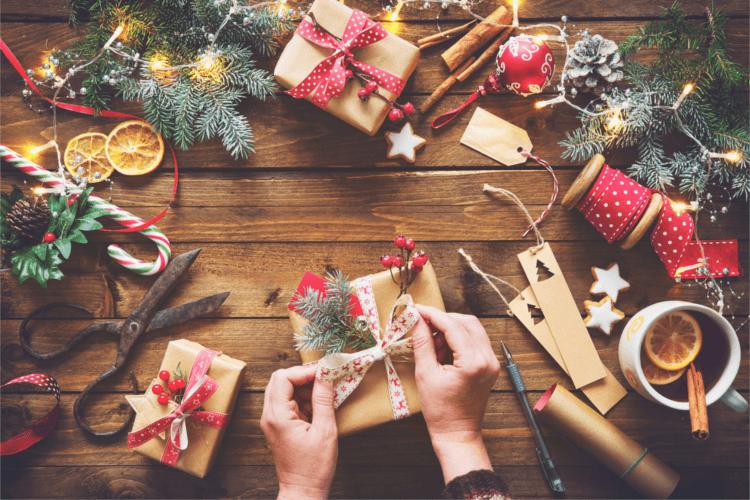 Zwei Hände, die ein Geschenk einpacken auf einem weihnachtlich dekorierten Tisch