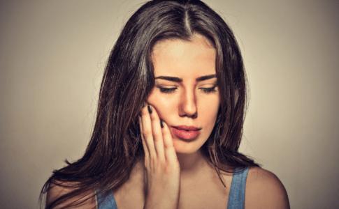 Frau fässt sich an die Wange und hat Schmerzen