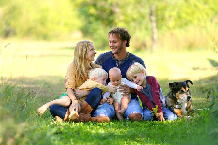 Glückliche Familie sitz mit ihrem Haustier im Grünen