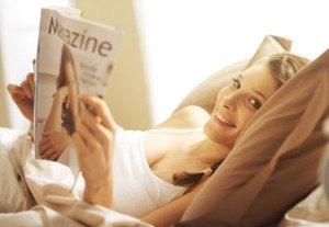 Frau im Bett mit Magazin