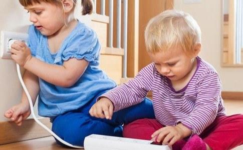 Kinder spielen mit Steckdose