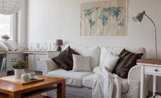 Gemütliches weißes Sofa mit Kissen und Decke