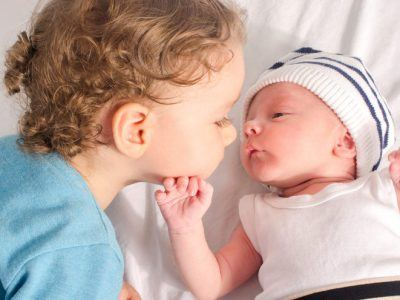 Loving toddler with his new born baby boy brother.