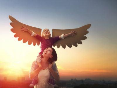 Was macht eine gute Mutter aus? - Mutter spielt mit Tocher mit Engelsflügeln aus Pappe