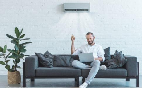 Klimaanlage vor der ein Mann sitzt