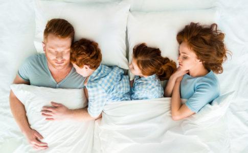 Familie liegt im Familienbett