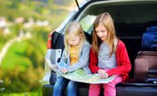 Zwei Kinder im Auto die auf eine Karte schauen
