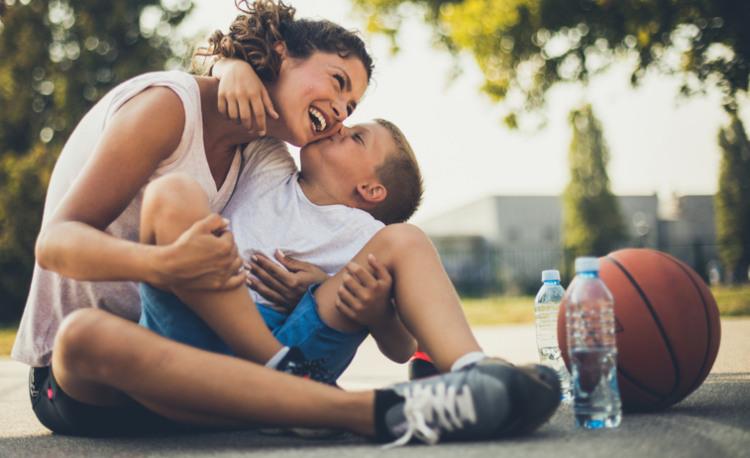 Mutter und Kind die sich vom Basketball spielen erholen