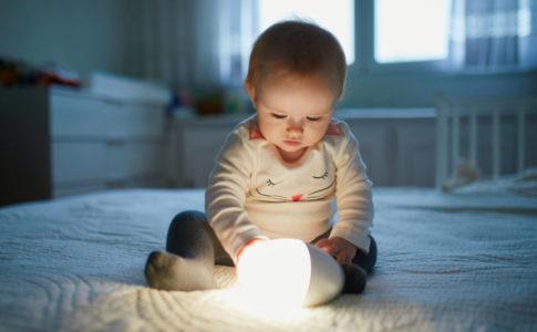 Kleines Baby welches eine Lampe hält