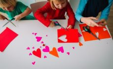 Zwei Kinder basteln Herzen aus Papier