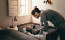 Mutter die Ihr Kind ins Babybett legt