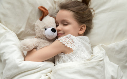 Kind welches einen Teddy umarmt