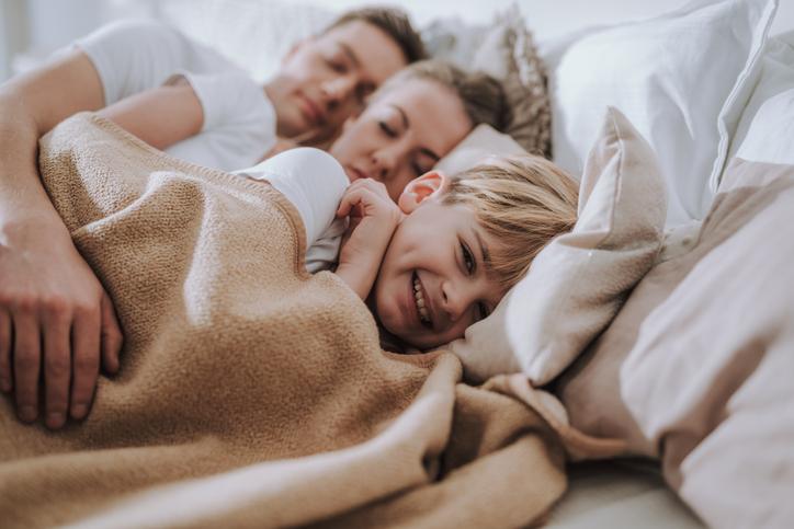 Kind liegt glücklich im Bett mit seinen Eltern