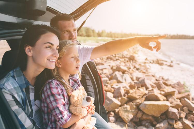 Familie sitzt im Kofferraum bei gutem Wetter