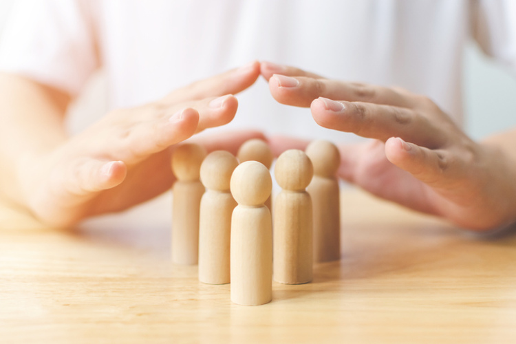 Holzfiguren die von einer Hand geschützt werden