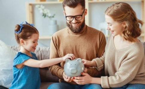 Familie wirft Geld in ein Sparschwein