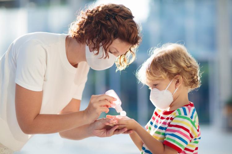 Mutter Kind mit Maske und Desinfektionsmittel