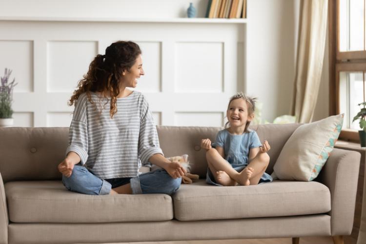 Mutter und Tochter meditieren auf dem Sofa