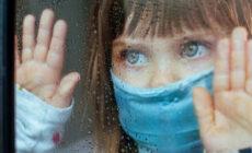 Kind am Fenster mit Maske