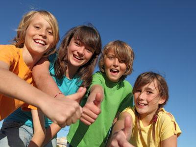 Fröhliche Kinder zeigen gemeinsam den Daumen nach oben