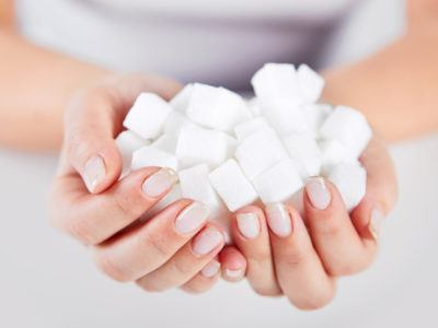 Frau hält Zuckerwürfel in der Hand