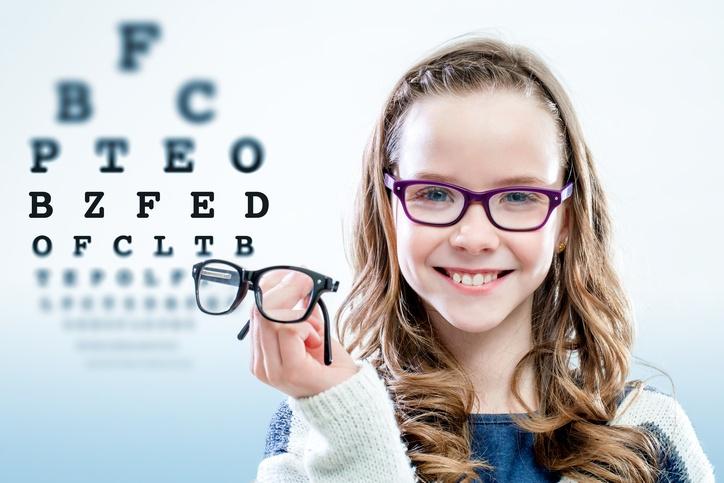 Kind hält Brille vor Sehtesttafel