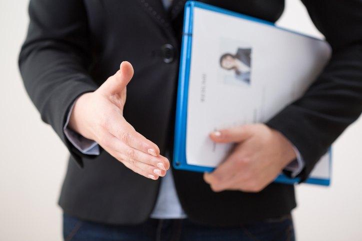 Frau streckt Hand zur Begrüßung aus und hält eine Bewerbungsmappe in der anderen Hand