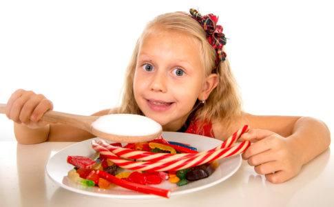 Kind mit einem Teller voll Süßigkeiten vor sich