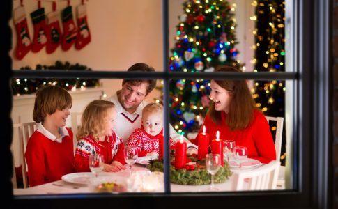 Familie mit Kleinkind beim Weihnachtsessen im Wohnzimmer