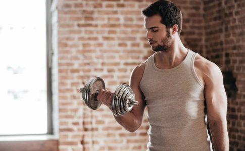 Mann trainiert mit Hantel zu Hause