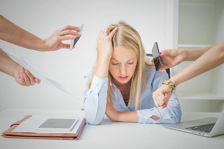 Frau sitzt überfordert und gestresst am Schreibtisch
