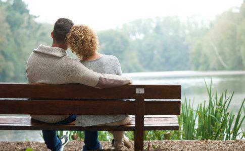 Kinderloses Paar sitzt auf einer Bank am See
