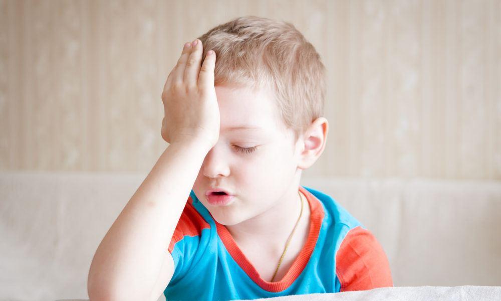Kleiner Junge hält sich vor Kopfschmerzen den Kopf